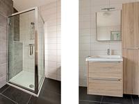 Geheel betegelde badkamer met wastafel, ligbad en douche en 2e toilet.