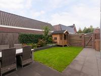 Leuk aangelegde, brede achtertuin voorzien van gazon en achterom.