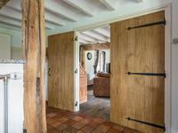 De leefkeuken en de woonkamer zijn van elkaar af te sluiten door de houten deuren te sluiten.