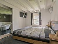 Achter het woongedeelte liggen de prive kamers, namelijk de riante slaapkamer met inloopkast en badkamer en suite. <BR>De slaapkamer is voorzien van tapijt, stucwerk wanden en een houten balken plafond en het genot van dat u meteen 's ochtends de badkamer inloopt.