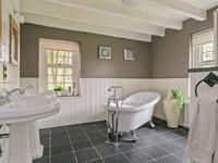In deze badkamer voorzien van een prachtig vrijstaand ligbad op pootjes, inloopdouche, 2e toilet en een dubbele wastafelcombinatie zult u ware rust ervaren. De vloer is voorzien van tegelwerk (met een eigen elektrische vloerverwarming) en de wanden van een houten lambrisering die samen met de gekozen kranen de boerderijsfeer afmaken. Mooi in een kast weggewerkt zit de aansluiting voor wasmachine en droger.