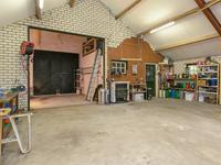 De grote vrijstaande garage met aparte stallingsruimte en hobbyschuur biedt u voldoende ruimte om lekker te klussen. De auto of aanhangwagen staat prima onder de carport. Achter de garage is een grote houtopslag - tuinhuis aanwezig welke in 2015 zijn geplaatst.