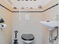 Aan de oprit zijde treft u het portaal met het deels betegelde toilet in jaren 20 stijl en de wasruimte.<BR>Desgewenst kunt u vanuit hier naar de achtergelegen praktijkruimte - studio.