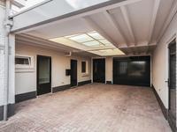 BUITEN DE WONING:<BR>De ruime bestrate oprit biedt volop parkeerplaatsen en toegang tot de garage en carport.<BR><BR>PRAKTIJKRUIMTE / STUDIO:<BR>Vanuit de carport is de achter het woonhuis gelegen bijgebouw bereikbaar. Thans is deze als studio in<BR>gebruik maar het kan natuurlijk ook uw eigen praktijkruimte worden. <BR>U komt binnen in de keuken met een tegelvloer en nette eenvoudige inrichting met kookplaat en afzuigkap. <BR>Aansluitend de wasruimte en opstelling Cv combi-ketel (2016). Op de verdieping is een woon-/ slaapkamer ingericht, betegelde douche, toilet en wasruimte, voldoende bergruimte en een deur naar het ruime dakterras met een mooi uitzicht op de tuin.