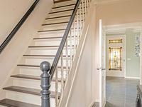 U komt binnen in een ruime hal met tegelvloer, een brede stijlvolle trap naar boven en een houten balken plafond. De uitgebreide moderne meterkast is naast de voordeur te vinden.