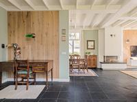 De verdiepte kelder is vanuit de kamer te bereiken en de schuifdeur met de handgeblazen glas-in-lood verbindt de kamer met de keuken.