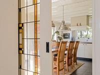 De grote woonkeuken, aangebouwd in 1991, ligt als het ware in uw tuin. Door de ramen en (tuin)deuren naar de tuin toe beleeft u hier het hele jaar door de seizoenen. Deze ruimte heeft een tegelvloer met vloer- en plintverwarming, een balkenplafond en een riant kookeiland met daarin de inductiekookplaat, kastruimte en daarboven de afzuigkap. <BR>Onder het raam staat de wandinrichting met daarin de koelkast, vriezer, combi-stoomoven en vaatwasser.