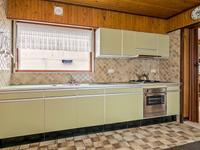 Aparte keuken met een tegelvloer en betegelde wanden heeft een eenvoudige keukeninrichting in een wandopstelling welke is voorzien van een dubbele spoelbak, gaskookplaat, afzuigkap en oven.