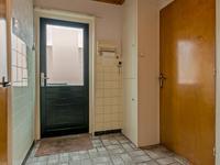De bijkeuken is voorzien van een tegelvloer en deels betegelde wanden en aansluitend treft u het deels betegelde toilet en de badkamer.