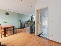Aansluitend is er toegang tot de L-vormige woonkamer welke voorzien is van stucwerk wanden en plafond met inbouwverlichting. Er is ruimschoots plaats voor een ruime zithoek en een fijne eethoek. Een houtkachel (ter overname) zorgt voor extra sfeer en warmte. Via een schuifpui is de achtertuin bereikbaar.