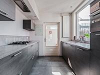 Aangrenzend aan de keuken is er een praktische ruimte met aansluiting voor de wasapparatuur. Via de achterdeur is er toegang tot de achtertuin.