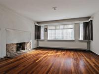 De doorzon woonkamer heeft een fijne lichtinval een houten begane grondvloer welke met parket is bedekt, een lichte plafondafwerking en openslaand deuren naar de serre.