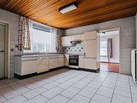 Linksaf kunt u naar de garage en rechtdoor wandelt u de woonkeuken binnen. Hier ligt diezelfde lichte tegelvloer en treft u een eenvoudige hoekkeuken met oven kookplaat en afzuigkap.