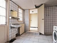 Vanuit de keuken komt u in een portaal met daarin het betegelde toilet en de eenvoudige douche. <BR>Achter het portaal is een ruime bijkeuken met cv opstelling, een wastafel, doorgang naar de inpandige werkkamer - berging en de inpandige garage met openslaande deuren en opstelling van de meterkast.