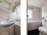 De badkamer is deels betegeld en uitgevoerd met een toilet, wastafel en ligbad.