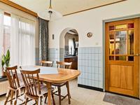 Mooie ruime woonkeuken met tegelvloer en deels betegelde wanden. De keuken is gesitueerd in de kooknis en is voorzien van een RVS aanrechtblad, gaskookplaat, afzuigkap, spoelbak, koelkast en oven.
