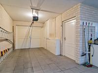 Tevens is vanuit het portaal een inpandige garage/berging (met elektrische openslaande deuren en tegelvloer) toegankelijk, met daarin o.a. de vloerverwarming unit, een stortbak en een zijdeur naar de tuin.