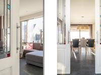 De twee schuifdeuren met glas-in-lood ramen naar de keuken zorgen ervoor dat deze kan worden afgesloten van de zithoek.