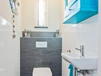 Achter de keuken, treft u de achterom, welke gedeeltelijk betegeld is, met toegang tot het toilet, de wasruimte en de inpandige garage. <BR><BR>Gedeeltelijk betegeld toilet met fonteintje.