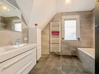 Geheel betegelde royale badkamer met een dubbele wastafelcombinatie, een ligbad en een inloopdouche met stortdouche en de luxe van massagesproeiers.