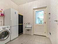 Praktische, volledig betegelde wasruimte met de aansluiting voor wasapparatuur, een uitstortgootsteen en de achterdeur met toegang naar het overdekte terras waar het ook in het voor- en najaar heerlijk toeven is.