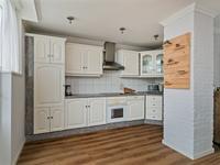 De keuken is een hoek opgesteld en voorzien van een electrische kookplaat, afzuigkap, oven, vaatwasser en koelkast.