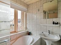 Geheel betegelde badkamer met een wastafel en ligbad met douchekraan-/mogelijkheid.