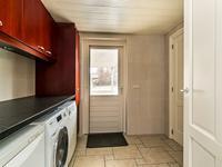 De geheel betegelde bijkeuken is ruim en beschikt over een wandmeubel met granieten werkblad, een garderobe, de aansluiting voor wasapparatuur en de achterdeur naar de tuin.