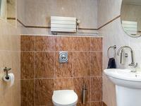 Geheel betegeld toilet met fonteintje.