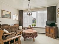 De woonkamer is voorzien van een schouw en dubbele beglazing. Er is voldoende plaats voor een zithoek en een ruime eethoek.