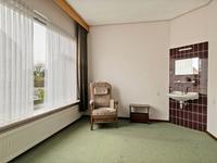 De slaapkamer op de begane grond is voorzien van een wastafel.