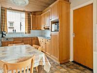 De eetkeuken, met een in een hoek opgestelde inrichting, beschikt over volop kastruimte, een granieten aanrechtblad met dubbele spoelbak, een keramische kookplaat, afzuigkap en koelkast.