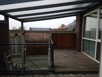 Aan de achterzijde is vanuit de kamer het dakterras toegankelijk met een houten vlonder en trap naar de patio beneden.