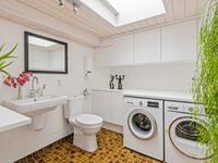 Vanuit de keuken komt u in de hal waar een grote toilet -/ wasruimte is ingericht.