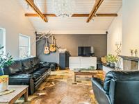 Over de volle breedte van het pand, aan de voorzijde, is de woonkamer gelegen met een tegelvloer, stucwerk wanden, en een houten schroten plafond. In de tv hoek rondom de schouw is het plafond opengelaten tot aan de nok.