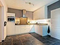 De woonkamer loopt door in de open keuken met mooie keukeninrichting in hoekopstelling voorzien van een koelkast, afzuigkap, gaskookplaat, combi-magnetron en vaatwasser. De keuken is voorzien van een gebrand granieten aanrechtblad. Vanuit de keuken heeft u via een schuifpui toegang tot de tuin.