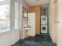 De keuken geeft daarnaast toegang tot een portaal met een kastenwand en via dit portaal bereikt u aan de ene zijde de bijkeuken (achter een schuifwand) waar zich de CV-installatie bevindt en een aansluiting voor de wasmachine en de droger.