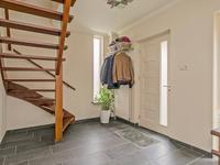 Open trap naar de eerste verdieping en toegang tot de woonkamer en de woon-/eetkeuken. Er bevindt zich in de hal een nieuwe meterkast.