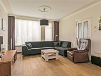 De doorzon woonkamer met een houten vloer is ruim, heeft spachtelputz wanden en een stucwerk plafond met diezelfde omlijsting. Er zitten voor en achter grote raampartijen waardoor er veel lichtinval in de kamer is.