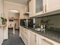 De keuken is voorzien van diezelfde tegelvloer, het aanrecht blad is van graniet en er zijn diverse inbouw apparaten aangebracht zoals de koelkast, vaatwasser, een inductiekookplaat en afzuigkap. Tevens is er een grote inbouwkast aanwezig.