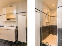 De badkamer is netjes, volledig betegeld en is voorzien van een ligbad, inloopdouche, 2e toilet en een wastafelmeubel.