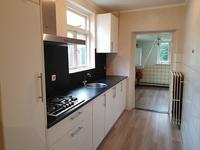 De dichte keuken is voorzien van een tegelvloer. De inrichting is in een wandopstelling geplaatst en voorzien van een gaskookplaat, afzuigkap en koelkast.