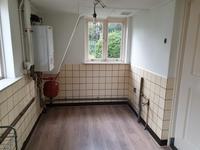 Vanuit de keuken is er toegang tot een bijkeuken voorzien van een laminaat vloer met de opstelling van de c.v.-installatie (Vaillant), de aansluiting voor de wasapparatuur en een achterdeur met toegang tot de tuin.
