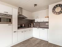 De open keuken staat in een hoekopstelling en is voorzien van een koelkast, 5-pits gasfornuis, rvs-afzuigkap, combi magnetron en vaatwasser. De diverse boven- en onderkasten zorgen ervoor dat er voldoende opbergruimte is.