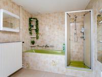 De royale badkamer is volledig betegeld en beschikt over een ligbad, een douchecabine, een closet en een wastafel. Tevens is hier een aansluiting voor de wasmachine en een deur met toegang tot een groot balkon.