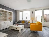 Vanuit de hal heeft u toegang tot de L-vormige leefruimte met  een open keuken aan de voorzijde en een tuingerichte woonkamer.<BR>De woonkamer en keuken zijn afgewerkt met diezelfde PVC-vloer en schuurwerk wanden en plafond.