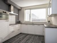 Aan de voorzijde bevindt zich de moderne keuken in een U-opstelling met volop werkruimte, bergruimte en een fraai zicht over het groen van de straat.  Uiteraard ontbreekt de apparatuur niet en is de keuken voorzien van een koelkast, inductie kookplaat, afzuigkap, combi magnetron en vaatwasser.