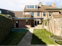 De zonnige achtertuin is verzorgd aangelegd: er is een overdekt terras met lichtstraat, kunstgras en een zithoek met vaste bank achter in de tuin waar het heerlijk toeven is.